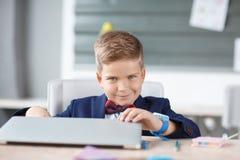 Un pequeño hombre de negocios abre un ordenador portátil en su lugar imagen de archivo