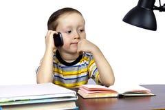 Un pequeño hombre de negocios en una oficina con el teléfono Fotografía de archivo libre de regalías