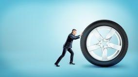 Un pequeño hombre de negocios que empuja hacia arriba en un nuevo neumático de coche enorme en fondo azul imagen de archivo