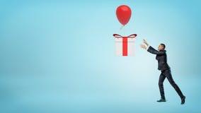 Un pequeño hombre de negocios que intenta coger una caja de regalo grande que está volando lejos en un globo Fotografía de archivo libre de regalías
