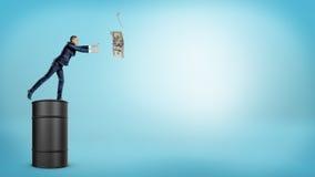 Un pequeño hombre de negocios que se coloca en un barril de aceite grande y que intenta coger un billete de dólar de un gancho de Foto de archivo libre de regalías
