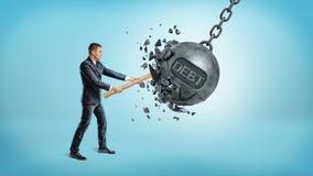 Un pequeño hombre de negocios rompe una bola de balanceo gigante del hierro con una palabra DEUDA en ella usando un martillo Fotografía de archivo libre de regalías