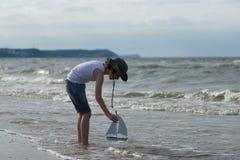 Un pequeño individuo en la playa arenosa Imagenes de archivo