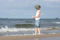 Un pequeño individuo en la playa arenosa Fotos de archivo libres de regalías