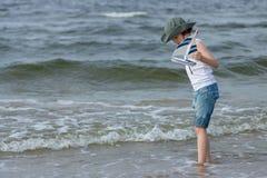 Un pequeño individuo en la playa arenosa Fotografía de archivo