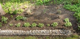 Un pequeño jardín cercado con las plantas cuidadosamente tendidas Fotografía de archivo