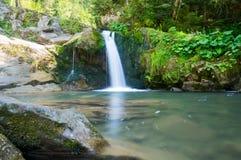 Un pequeño lago con una cascada en las montañas Imagen de archivo libre de regalías