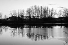 Un pequeño lago en invierno, con hielo en la superficie y el reflec de los árboles Imagen de archivo libre de regalías
