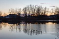 Un pequeño lago en la puesta del sol en invierno, con hielo en la superficie y el tr Imagenes de archivo