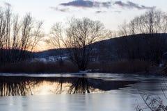 Un pequeño lago en la puesta del sol en invierno, con hielo en la superficie y el tr Imágenes de archivo libres de regalías