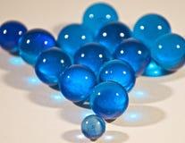 Un pequeño mármol azul que lleva a un grupo más grande Imagen de archivo libre de regalías