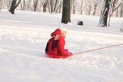Un pequeño montar a caballo del niño en el trineo en nieve Imagen de archivo libre de regalías