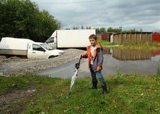 Un pequeño muchacho con el paraguas que se coloca cerca del camino y de los coches inundados Imagen de archivo libre de regalías