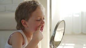 Un pequeño muchacho con el pelo rubio con el espejo que abre su boca para mostrar donde él perdió uno de sus dientes de bebé almacen de metraje de vídeo