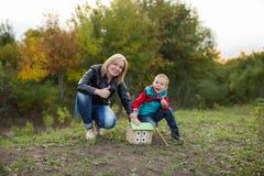Un pequeño muchacho con su madre en el bosque del otoño recolectó una madera Fotografía de archivo libre de regalías