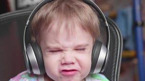 Un pequeño muchacho divertido se sienta en una silla y escucha la música a través de los auriculares Ascendente cercano de la car metrajes