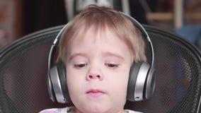 Un pequeño muchacho divertido se sienta en una silla y escucha la música a través de los auriculares Ascendente cercano de la car almacen de metraje de vídeo