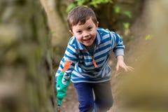 Un pequeño muchacho en ropa brillante sube a través de un bosque mientras que sonríe imagen de archivo libre de regalías