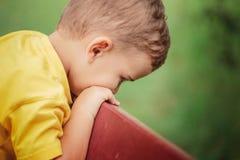 Un pequeño muchacho en una camiseta amarilla se está sentando en un banco de parque y triste Primer Imagen de archivo libre de regalías