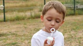 Un pequeño muchacho lindo se sienta en un banco en el parque e infla lentamente burbujas de jabón La cara del cierre del niño par metrajes