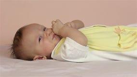 Un pequeño muchacho recién nacido lindo miente en su parte posterior y juegos con un juguete él mira la cámara almacen de video