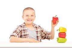 Un pequeño muchacho sonriente que sostiene las pimientas coloridas en una tabla Fotografía de archivo libre de regalías