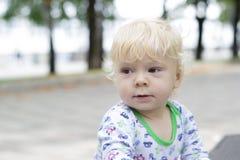 Un pequeño niño aprende caminar cerca de los bancos, niño Foto de archivo