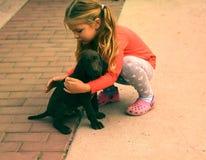 Un pequeño niño blanco caucásico hermoso de la muchacha con el pelo rubio largo y el pequeño perrito del indicador imágenes de archivo libres de regalías