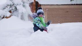 Un pequeño niño camina en el parque del invierno Bebé que juega y sonriente en la nieve mullida blanca Resto y juegos activos almacen de video