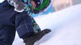 Un pequeño niño camina en el parque del invierno El bebé que juega y sonriente sube para arriba la colina, cayendo otra vez las s almacen de video