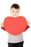Un pequeño niño coloca y lleva a cabo el corazón Imagen de archivo