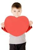Un pequeño niño coloca y lleva a cabo el corazón Imagen de archivo libre de regalías
