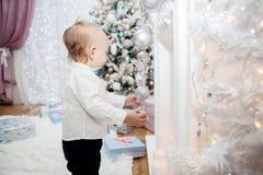 Un pequeño niño con las decoraciones de la Navidad en un interior festivo ` S del Año Nuevo y la Navidad Fotos de archivo libres de regalías