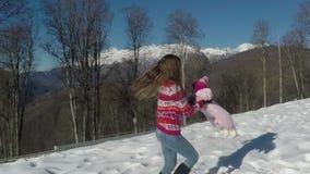 Un pequeño niño con su madre que juega en la nieve metrajes