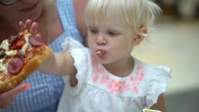 Un pequeño niño en un café de los alimentos de preparación rápida come la pizza Consumición divertida del niño del retrato lindo  metrajes