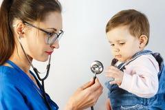 Un pequeño niño en el examen en el doctor mira el estetoscopio y tira de su mano a él imagenes de archivo