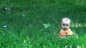 Un pequeño niño en la hierba en el parque almacen de metraje de vídeo