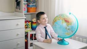 Un pequeño niño está buscando un lugar en el globo en donde él creció almacen de video