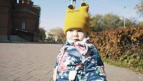 Un pequeño niño está caminando solamente en un parque del otoño metrajes