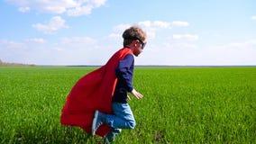 Un pequeño niño feliz en un traje del super héroe, una capa roja y una máscara corre en hierba verde contra un cielo azul almacen de metraje de vídeo