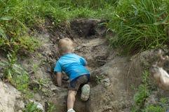 Un pequeño niño hace un esfuerzo para subir la montaña imagenes de archivo