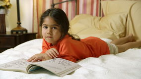 Un pequeño niño hispánico lindo que miente en cama goza de su libro de trabajo de la diversión almacen de metraje de vídeo