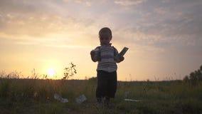 Un pequeño niño lanza cientos billetes de dólar alrededor de él en la cámara lenta en la puesta del sol metrajes