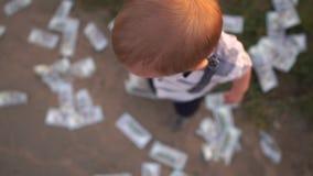 Un pequeño niño lanza cientos billetes de dólar alrededor de él en la cámara lenta almacen de video