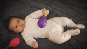 Un pequeño niño miente en la opinión superior del sofá Muchacha en un traje ligero metrajes