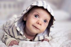 Un pequeño niño miente en su estómago, parece interesante y sonríe Fotografía de archivo