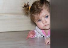 Un pequeño niño mira a escondidas hacia fuera de detrás el guardarropa La muchacha con el pelo largo Imagen de archivo