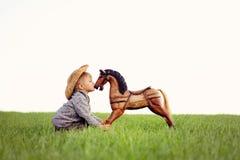 Un pequeño niño, un muchacho está besando un caballo mecedora en un prado La niñez feliz en el campo, el niño se ocupa su animal  imagen de archivo libre de regalías