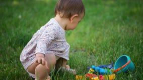Un peque?o ni?o o beb? de la muchacha en el vestido que juega al aire libre con los juguetes pl?sticos de la arena, actividad de  metrajes