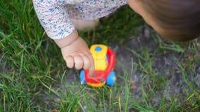 Un peque?o ni?o o beb? de la muchacha en el vestido que juega al aire libre con los juguetes pl?sticos del coche, actividad de la metrajes